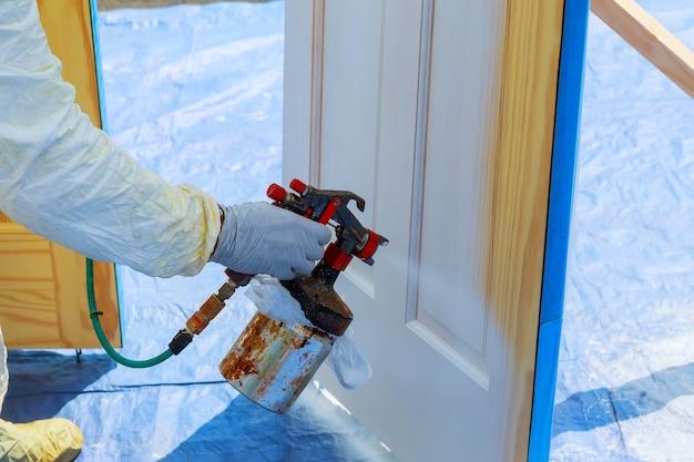 Réparation De La Maison Peindre La Porte En Bois De Couleur Blanche Avec Un Spray Photo Premium