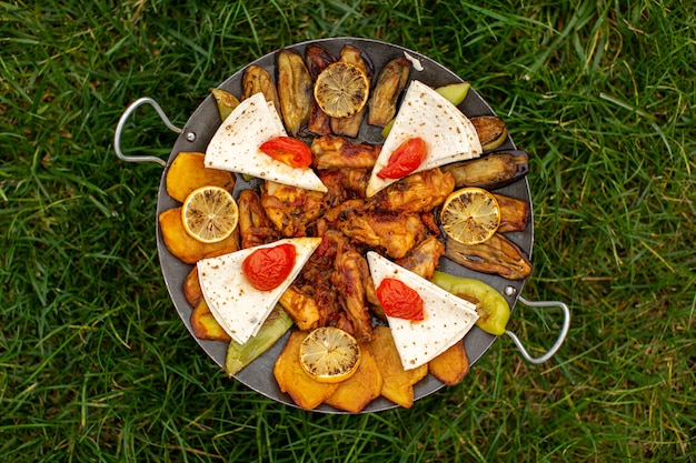 Un Repas Cuit Vue De Dessus Avec De La Viande Et Des Légumes à L'intérieur Du Moule Sur L'herbe Verte Photo gratuit