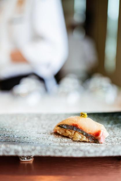 Repas Japonais Omakase Shima Aji Sushi Avec Wasabi Frais Servi à La Main Sur Une Plaque Noire En Pierre. Photo Premium