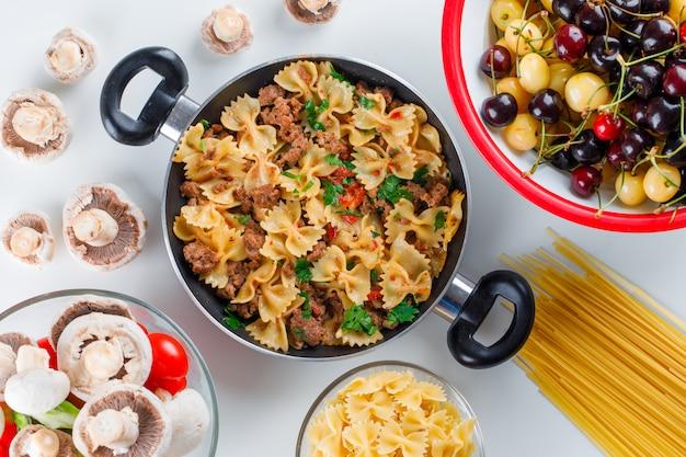Repas De Pâtes Dans Une Poêle Avec Des Pâtes Crues, Champignons, Poivrons, Tomates, Cerises Photo gratuit