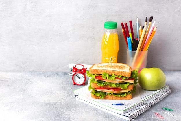 Repas sain pour l'école avec sandwich, pomme fraîche et jus d'orange. Photo Premium