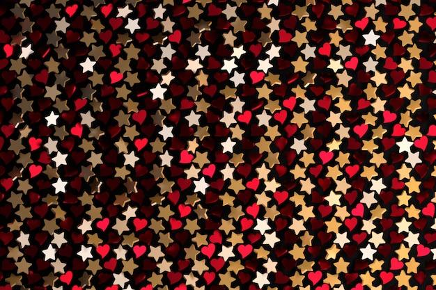 Répétant Les étoiles D'or Et Les Coeurs Rouges Sur Fond Noir. Photo Premium