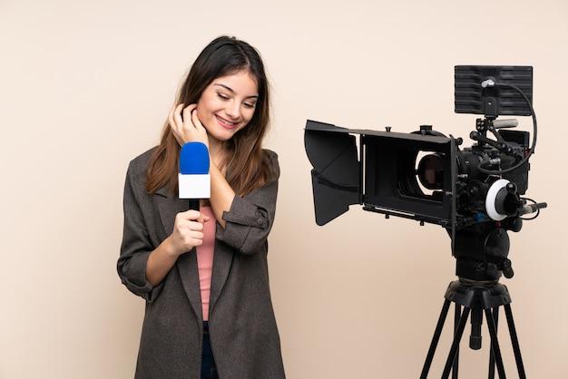 Reporter Femme Tenant Un Microphone Et Rapportant Des Nouvelles Sur Le Mur Isolé En Riant Photo Premium