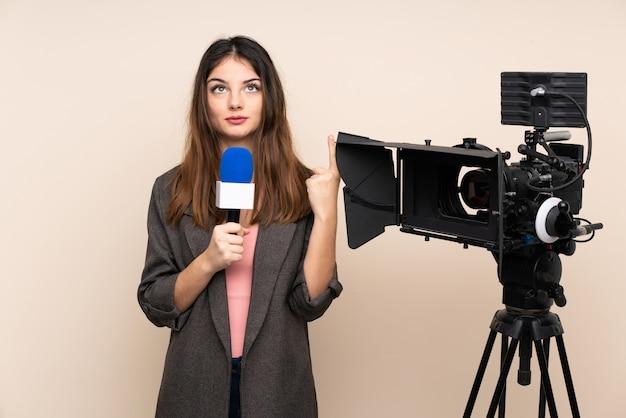 Reporter Femme Tenant Un Microphone Et Rapportant Des Nouvelles Sur Le Mur Pointant Avec L'index Photo Premium