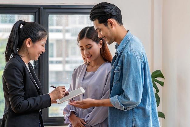 Le représentant de vente offre la liste de prix de l'immobilier et la condition d'achat ou de location du contact Photo Premium