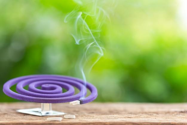 Répulsif violet anti-moustiques sur une table en bois avec fond d'espace de lumière flou vert Photo Premium