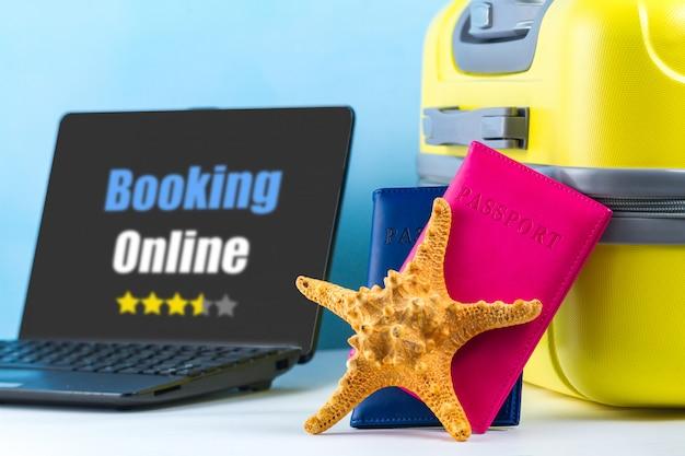 Reservation en ligne. commandez des billets et réservez des hôtels en ligne. une valise de voyage jaune vif, des passeports, un ordinateur portable et un coquillage. concept de voyage Photo Premium