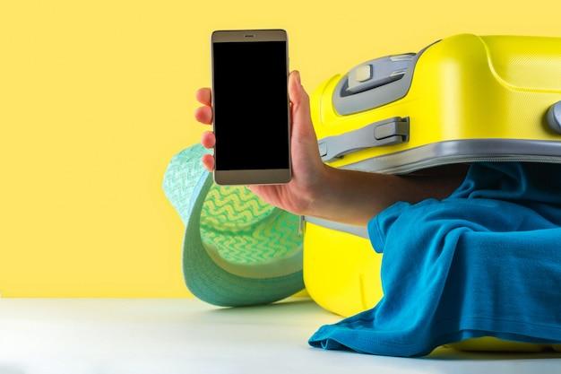 Reservation en ligne. réservation de billets et d'hôtels sur internet. valise de voyage pleine de vêtements sur un vif. concept de voyage. loisirs, vacances Photo Premium