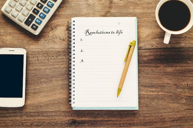 Résolutions au texte de la vie sur la note du livre avec une tasse de café, stylo Photo Premium