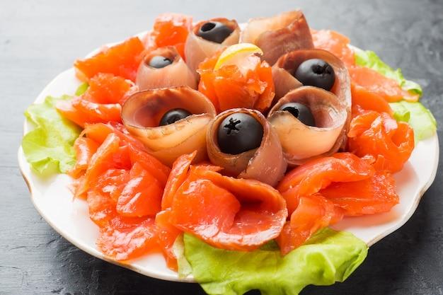 Restaurant gastronomique servant une assiette de sel fumé, filets de poisson blanc cru et saumon Photo Premium