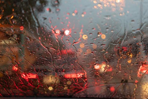 Résumé floue la pluie alors que la voiture est au milieu de la route la nuit Photo Premium