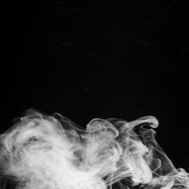 Résumé des fumées de fumée blanche sur fond noir Photo gratuit