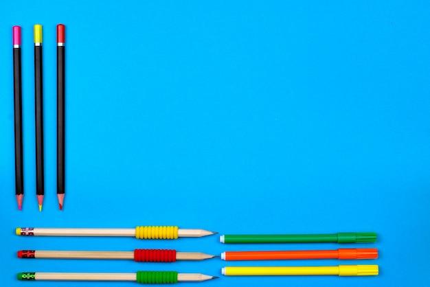 Retour au concept de l'école: cadre avec des crayons de couleur et des crayons sur un fond bleu Photo Premium