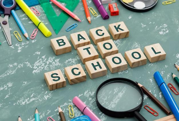 Retour Au Concept De L'école Avec Des Cubes En Bois, Loupe, Fournitures Scolaires Sur Fond De Plâtre Vue En Plongée. Photo gratuit