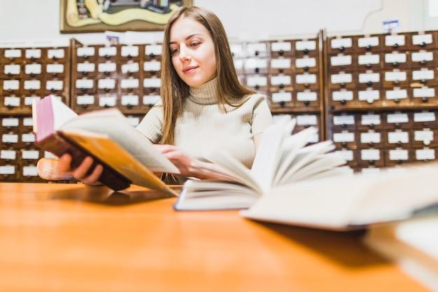 Retour au concept d'école avec une femme étudiant en bibliothèque Photo gratuit