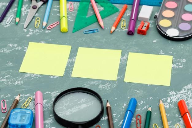 Retour Au Concept De L'école Avec Des Notes Autocollantes, Loupe, Fournitures Scolaires Sur Fond De Plâtre Vue En Plongée. Photo gratuit