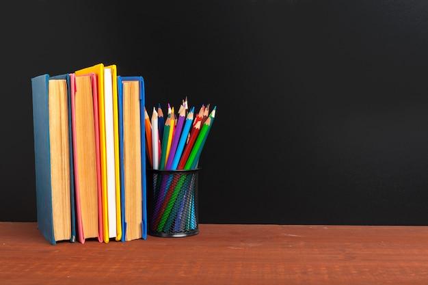 Retour au fond du concept d'école. tableau noir avec des livres et pomme sur un bureau en bois Photo Premium