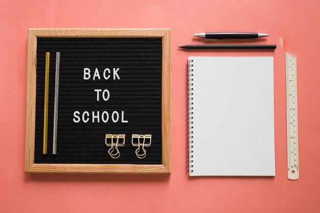 Retour Au Texte De L'école Sur L'ardoise Avec Des Articles De Papeterie Sur Fond Coloré Photo gratuit