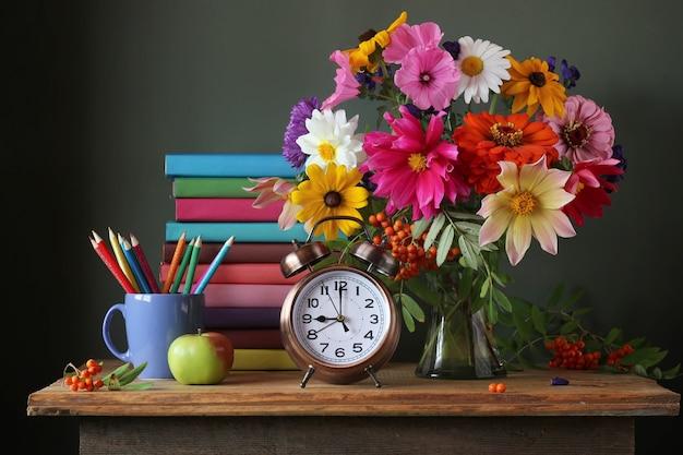 Retour à l'école. 1er septembre, journée du savoir. la journée de l'enseignant nature morte avec bouquet d'automne et fournitures scolaires. manuels scolaires. Photo Premium