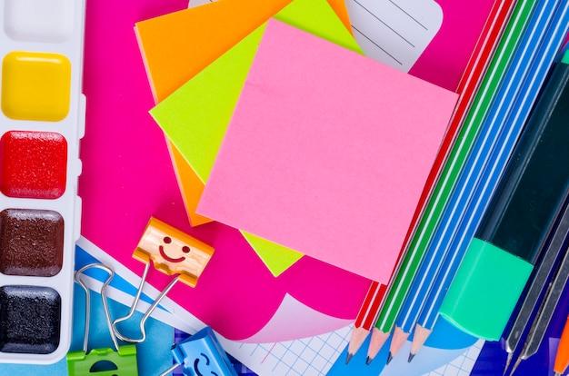 De retour à l'école avec des accessoires scolaires - peintures, crayons, cahiers, ciseaux, marqueurs, bleu. Photo Premium