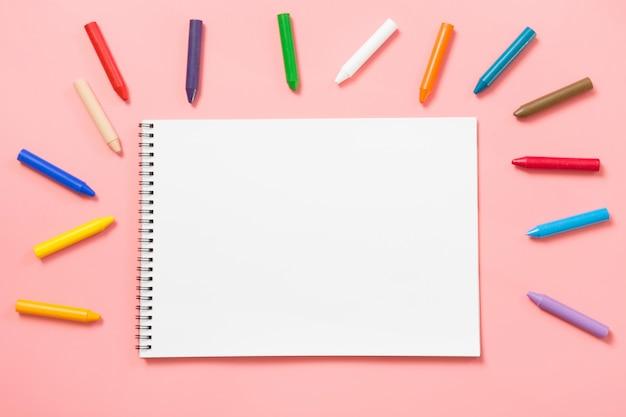 Retour à l'école. crayons à la cire colorés et album sur rose pastel. Photo Premium