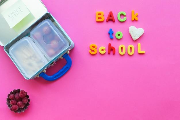 Retour à l'école écrit près de lunchbox et de framboises Photo gratuit