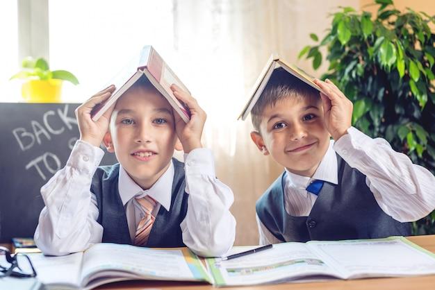 Retour à l'école. enfants mignons assis au bureau dans la classe. Photo Premium