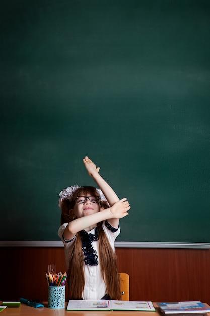 Retour à l'école. la fille au bureau lève le bras Photo Premium