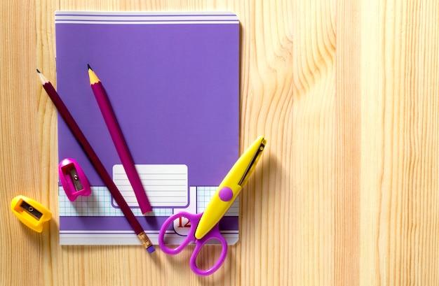 Retour à l'école. fournitures scolaires sur une planche de bois. Photo Premium