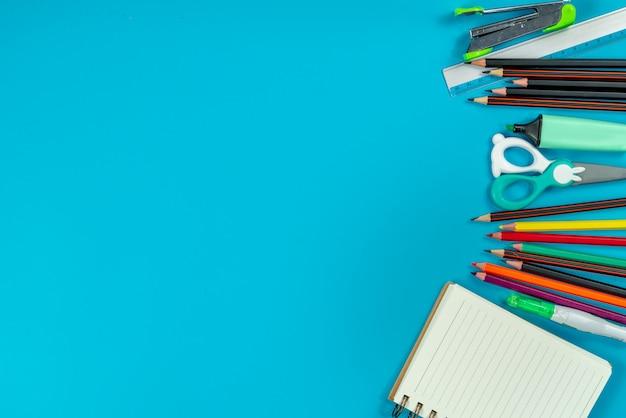 Retour à l'école . fournitures scolaires et tableau noir sur bleu Photo Premium