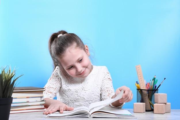 Retour à L'école. Heureux Enfant Industrieux Mignon Est Assis à Un Bureau à L'intérieur. L'enfant Apprend En Classe. Photo Premium