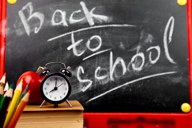 Retour à l'école lettrage sur tableau noir avec un morceau de craie Photo Premium