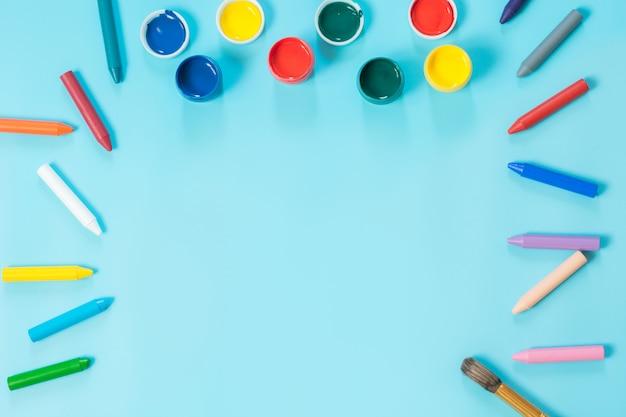 Retour à l'école. peinture colorée et pinceau en bleu percutant. espace de copie. vue de dessus. Photo Premium