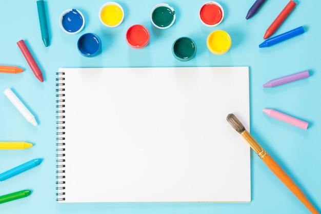 Retour à l'école. peintures colorées, album et pinceau sur bleu percutant. espace de copie. vue de dessus. Photo Premium
