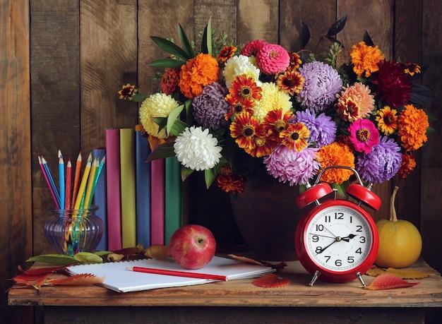 Retour à l'école. réveil, bouquet, pommes et livres sur la table. la journée de l'enseignant le jour de la connaissance Photo Premium