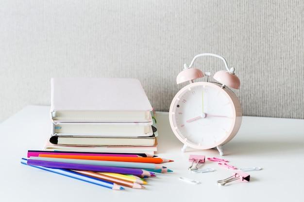 Retour à l'école sur la table blanche. livres, crayons, réveil sur le bureau. Photo Premium