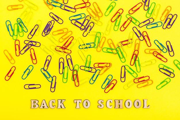 Retour à L'école. Trombones Colorés Sur Fond Jaune Au Hasard Et Phrase En Lettres En Bois Photo Premium