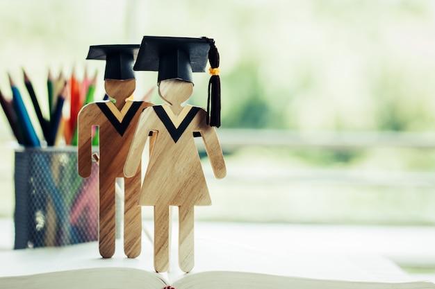 Retour à la notion d'école, deux personnes signent bois avec graduation fête casquette sur manuel ouvert Photo Premium