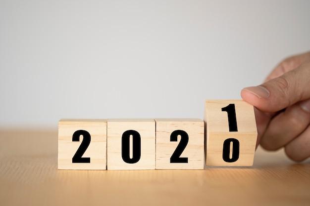 Retournement Manuel De Blocs De Bois Pour L'année De Changement 2020 à 2021. Concept De Nouvel An Et Vacances. Photo Premium
