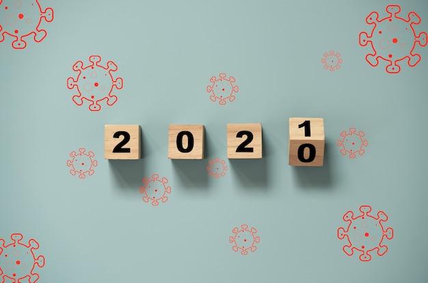 Retourner Un Bloc De Cubes En Bois Pour Changer L'année 2020 à 2021 Avec Le Virus Corona. Bonne Année Ensemble Covid-19 Ou Situation Pandémique Du Virus Corona. Photo Premium