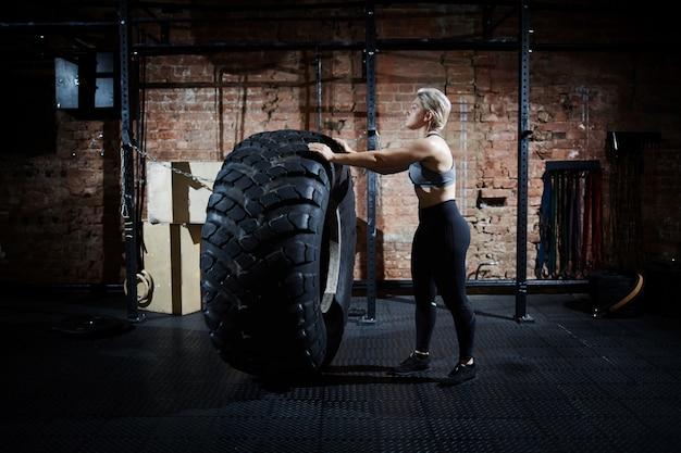 Retourner un pneu dans un gymnase Photo gratuit