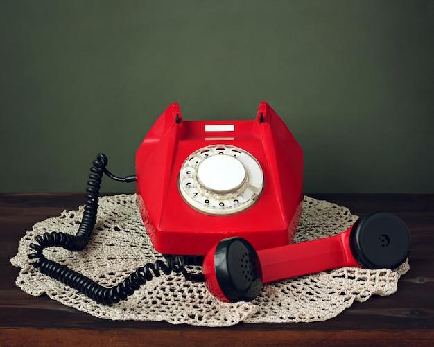 Rétro téléphone rotatif rétro avec le récepteur pris sur une serviette en dentelle Photo Premium