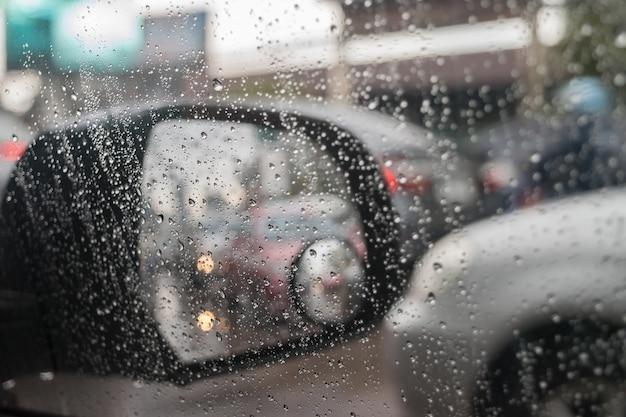 Rétroviseur de voiture pour vue arrière et l'eau de pluie tombe avec fond de réflexion de la circulation Photo Premium