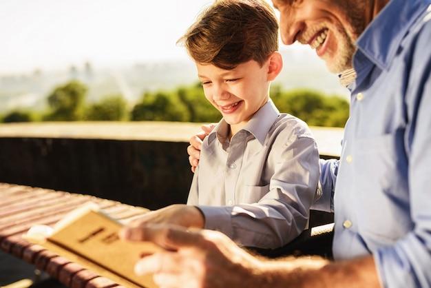 Réunion de famille à park guys read book together Photo Premium