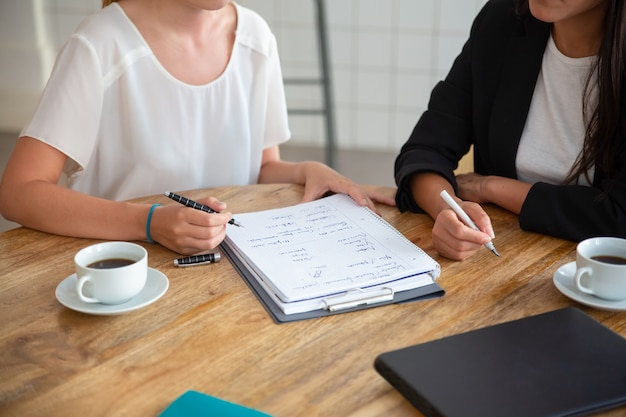 Réunion De Jeunes Collègues Féminines Et Discuter Du Plan D'affaires, Rédiger Un Schéma Stratégique Sur Papier, Faire Un Projet Photo gratuit