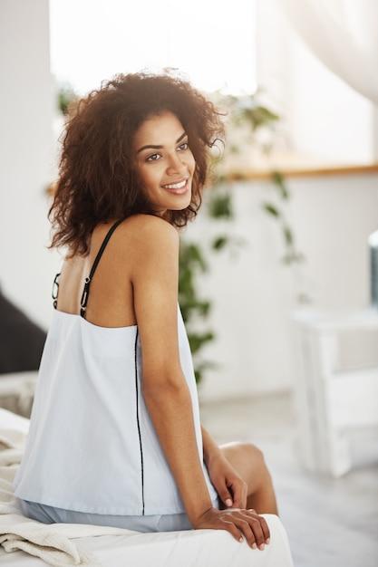 Rêve Tendre Femme Africaine En Vêtements De Nuit Assis Sur Le Lit Le Matin En Souriant La Pensée. Photo gratuit