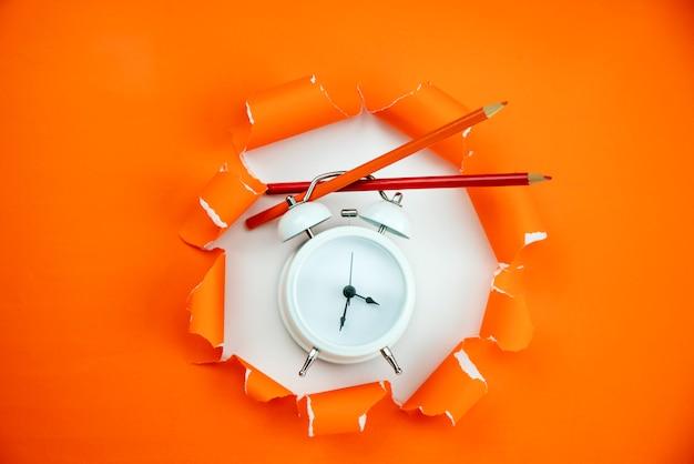 Réveil blanc avec des crayons sur fond de papier ouvert déchiré orange Photo Premium
