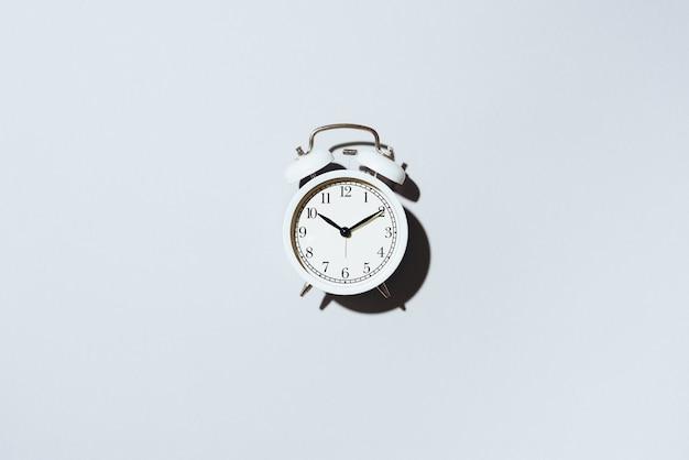 Réveil blanc avec une ombre forte sur fond gris. Photo Premium