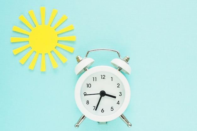 Réveil blanc et soleil de papier jaune sur un fond de papier bleu. espace pour le texte. Photo Premium