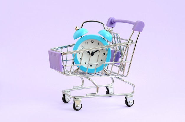 Réveil bleu en chariot de supermarché sur fond violet Photo Premium